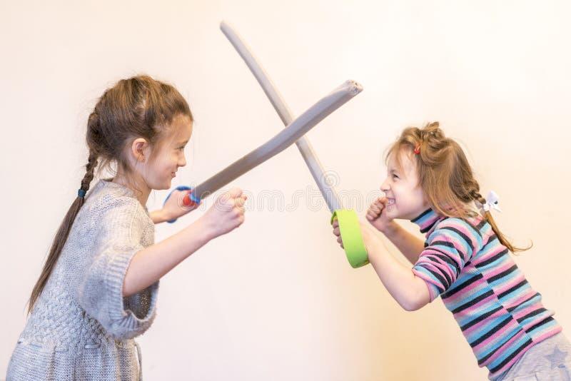 Dos muchachas con los caballeros del juego de las espadas del juguete Children& x27; emociones de s fotografía de archivo libre de regalías