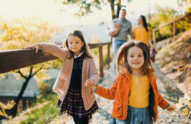 Dos muchachas con los padres irreconocibles en el fondo que caminan en parque en otoño fotos de archivo
