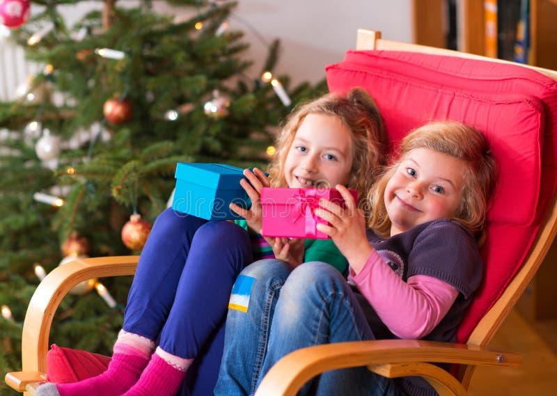 Dos muchachas con los presentes delante del árbol de navidad fotos de archivo