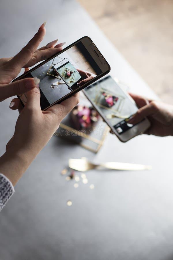 Dos muchachas con los teléfonos en manos toman la imagen del pedazo de torta hermoso foto de archivo