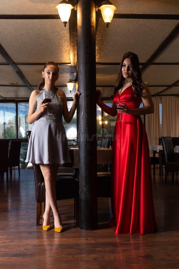 Dos muchachas con los vidrios de vino tinto que presentan en el restaurante retro imágenes de archivo libres de regalías