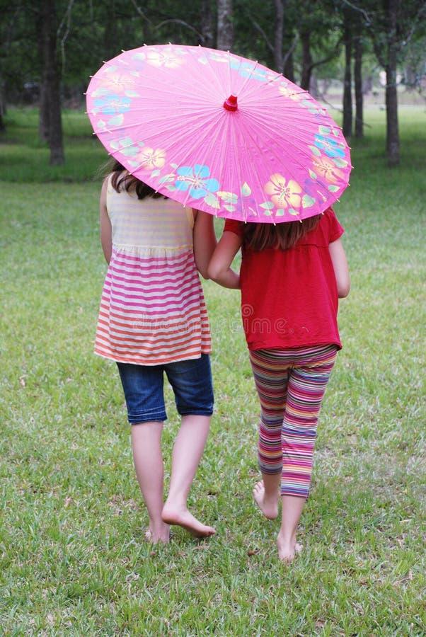 Dos muchachas con un paraguas foto de archivo