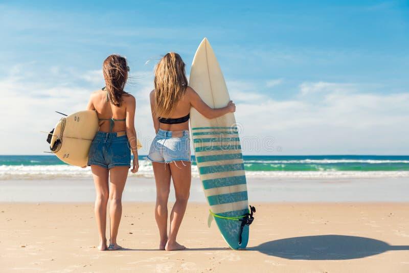 Dos muchachas de la persona que practica surf en la playa foto de archivo libre de regalías