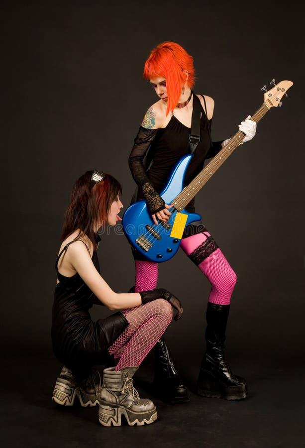 Dos muchachas de la roca, uno de ellos que lamen la guitarra fotografía de archivo libre de regalías