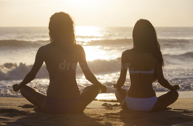 Dos muchachas de las mujeres del bikini que sientan la playa de la salida del sol de la puesta del sol imagenes de archivo