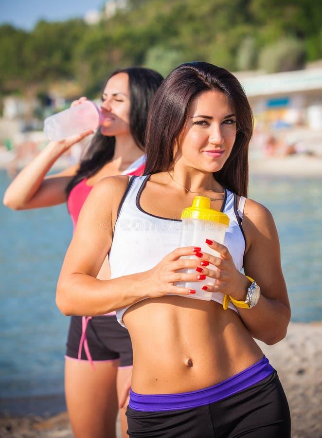 Dos muchachas de los deportes en una playa fotos de archivo