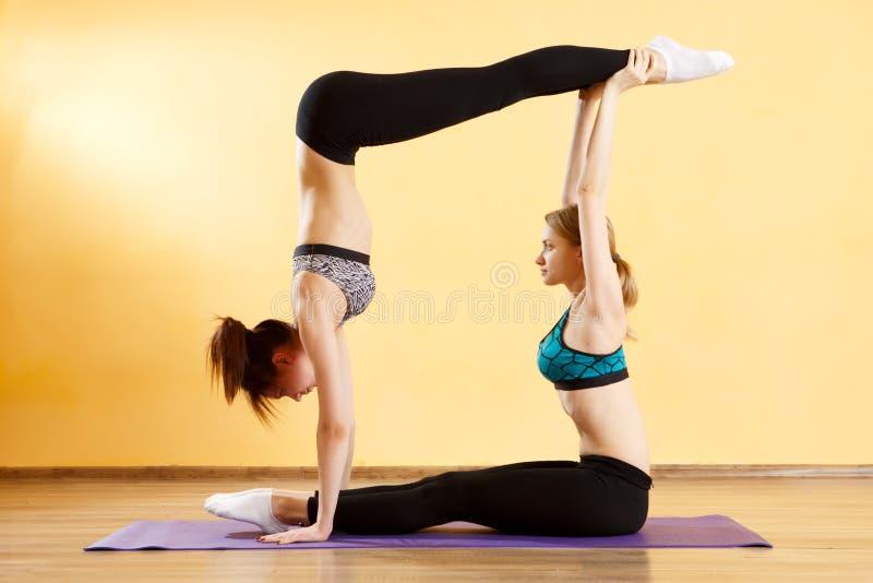 Dos muchachas de los deportes que hacen yoga fotos de archivo
