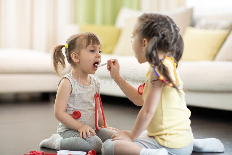 Dos muchachas de los niños que juegan al doctor en casa La niña pequeña abre su boca y dice el aaah Muchacha del niño que examina imagen de archivo libre de regalías