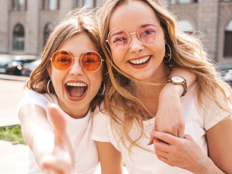 Dos muchachas de moda hermosas que presentan en la calle foto de archivo