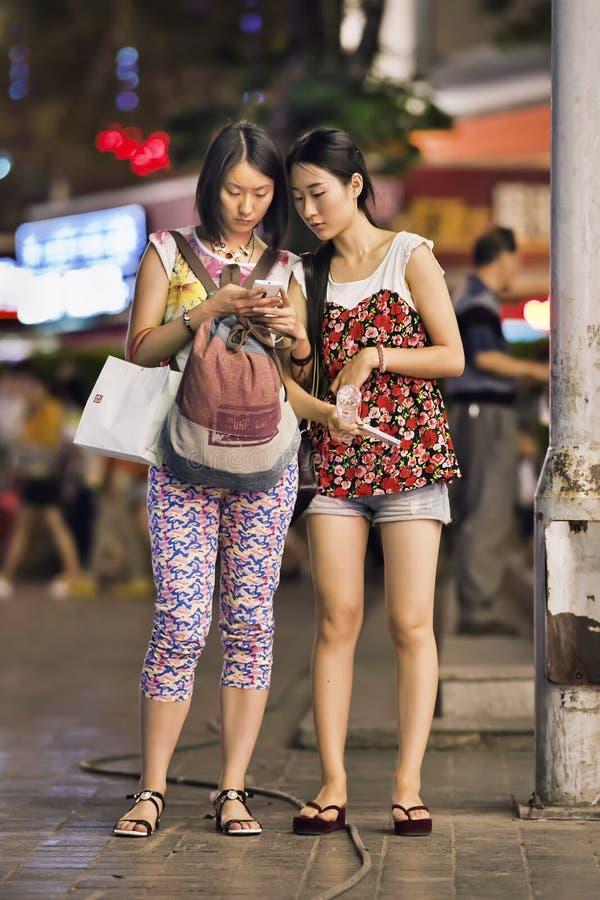 Dos muchachas de moda ocupadas con el teléfono elegante en centro de la ciudad, Kunming, China fotos de archivo libres de regalías