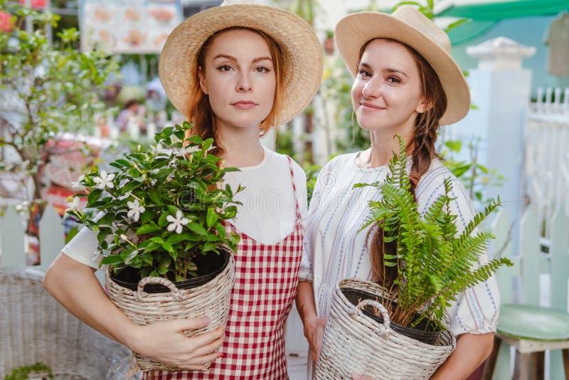 Dos muchachas del jardinero que llevan las plantas fotografía de archivo