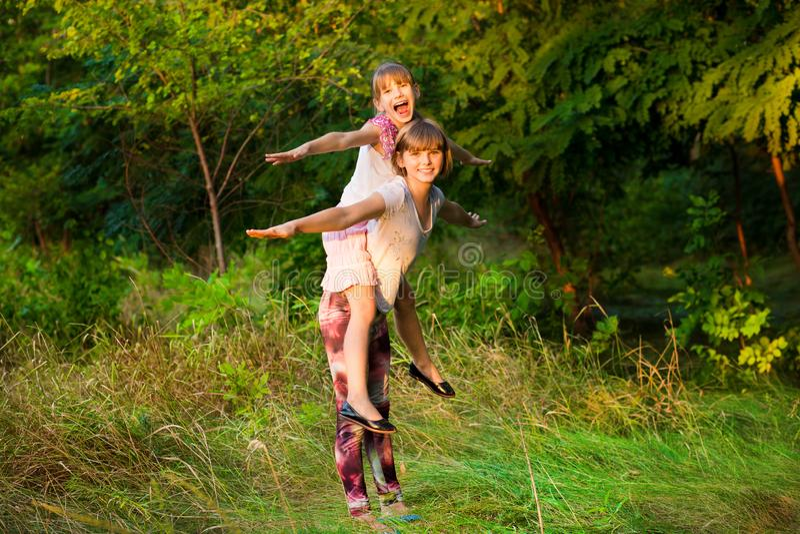 Dos muchachas del niño que juegan junto Las hermanas juegan al super héroe Niños felices que tienen la diversión, la sonrisa y ab foto de archivo libre de regalías