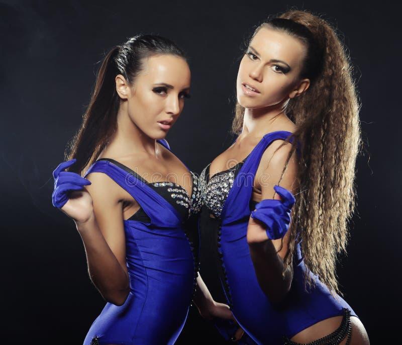 Dos muchachas del 'strip-tease' sobre fondo oscuro fotografía de archivo