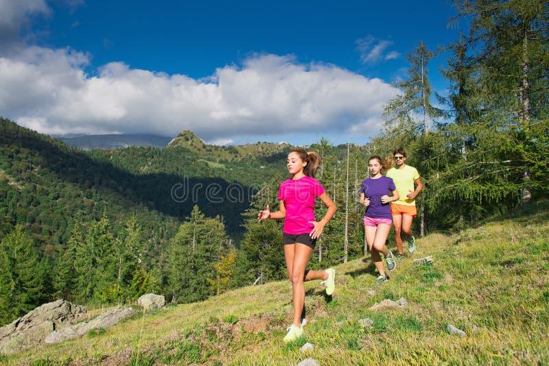Dos muchachas deportivas jovenes y un muchacho que corre junto en la hierba i fotos de archivo