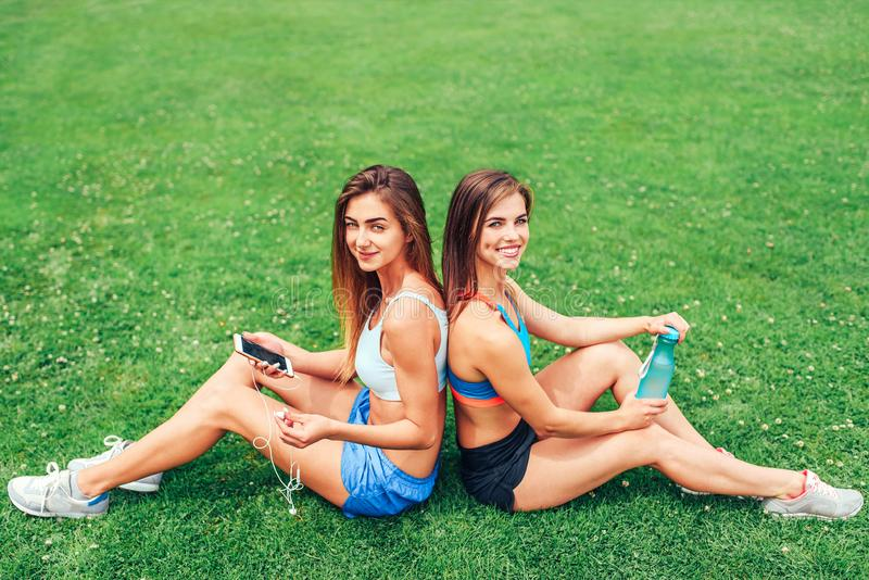 Dos muchachas deportivas lindas que se relajan después del entrenamiento al aire libre fotos de archivo