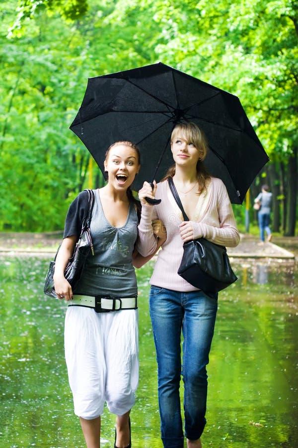 Dos muchachas disfrutan al tiempo lluvioso imágenes de archivo libres de regalías