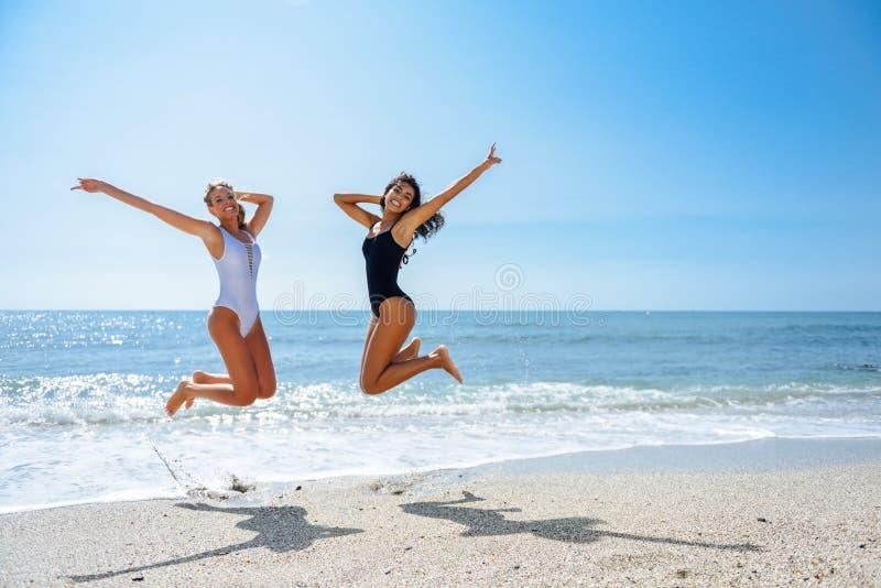 Dos muchachas divertidas en el traje de baño que salta en una playa tropical fotografía de archivo libre de regalías