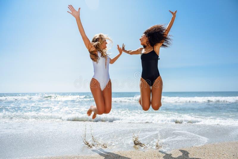 Dos muchachas divertidas en el traje de ba?o que salta en una playa tropical imágenes de archivo libres de regalías
