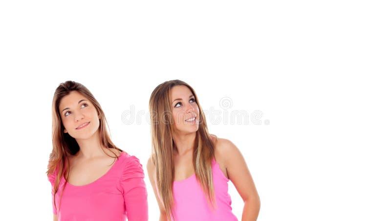 Dos muchachas en el rosa que mira para arriba imagen de archivo