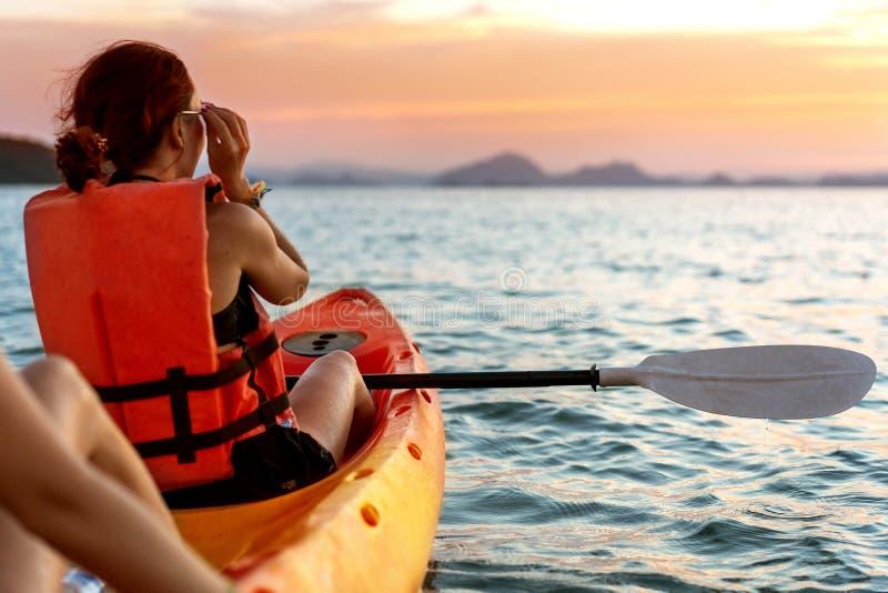 Dos muchachas en kajaks en el mar en la puesta del sol fotografía de archivo libre de regalías