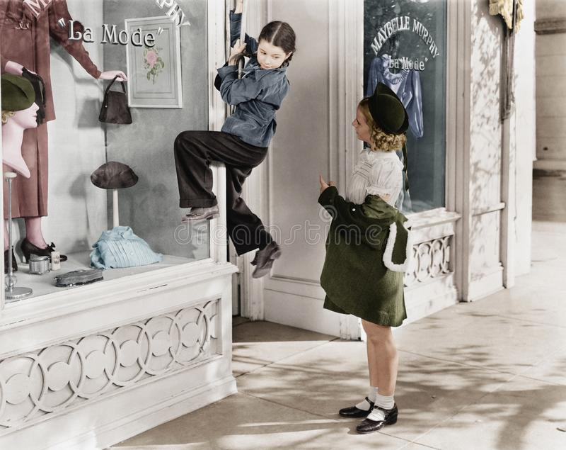 Dos muchachas en la calle con una que sube en una ventana de exhibición (todas las personas representadas no son vivas más largo  fotografía de archivo