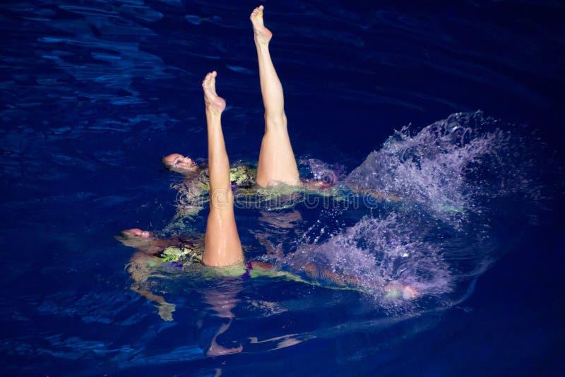 Dos muchachas en la piscina que se realiza en los campeones olímpicos de la demostración imágenes de archivo libres de regalías