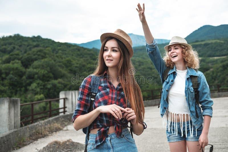 Dos muchachas en los sombreros que viajan y que hacen autostop foto de archivo