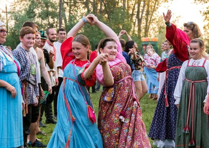 Dos muchachas en los trajes rusos coloridos, bailando en una muchedumbre por la época del festival internacional anual de la músi fotografía de archivo libre de regalías