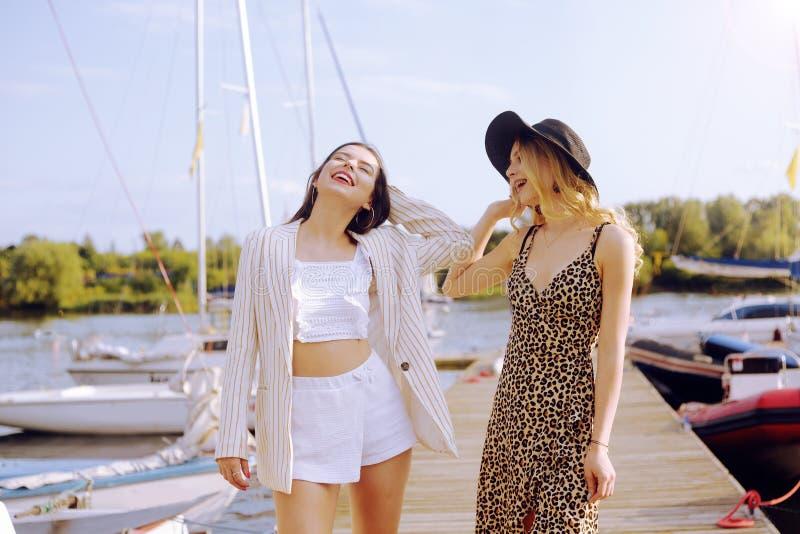 Dos muchachas en los yates del fondo, barcos de navegación son sonrisa, mirando la cámara Morenita en un sombrero y una chaqueta  imagen de archivo