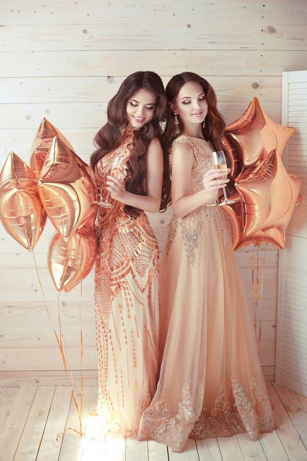 Dos muchachas en partido Mujeres jovenes hermosas en dres de oro elegantes fotografía de archivo