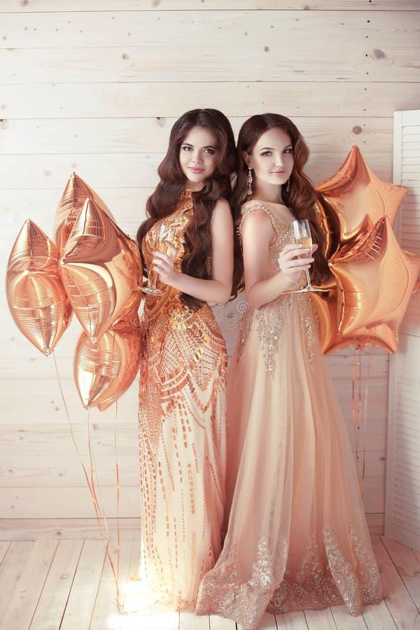 Dos muchachas en partido Mujeres jovenes hermosas en dres de oro elegantes fotos de archivo libres de regalías