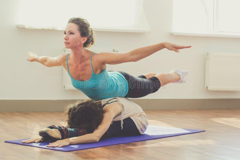 Dos muchachas están haciendo yoga dentro foto de archivo libre de regalías