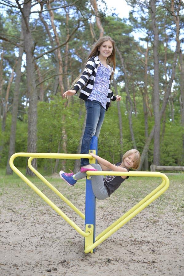 Dos muchachas están jugando en el patio en la atracción del metal amarillo Es ventoso imágenes de archivo libres de regalías