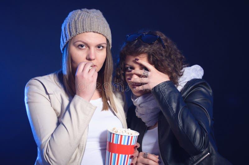 Dos muchachas están mirando película de terror en cine foto de archivo