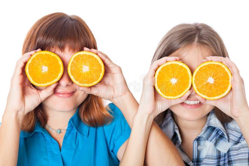 Dos muchachas están mirando a través de naranjas imagenes de archivo