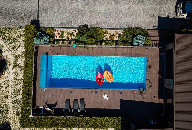 Dos muchachas están nadando en la piscina fotografía de archivo libre de regalías