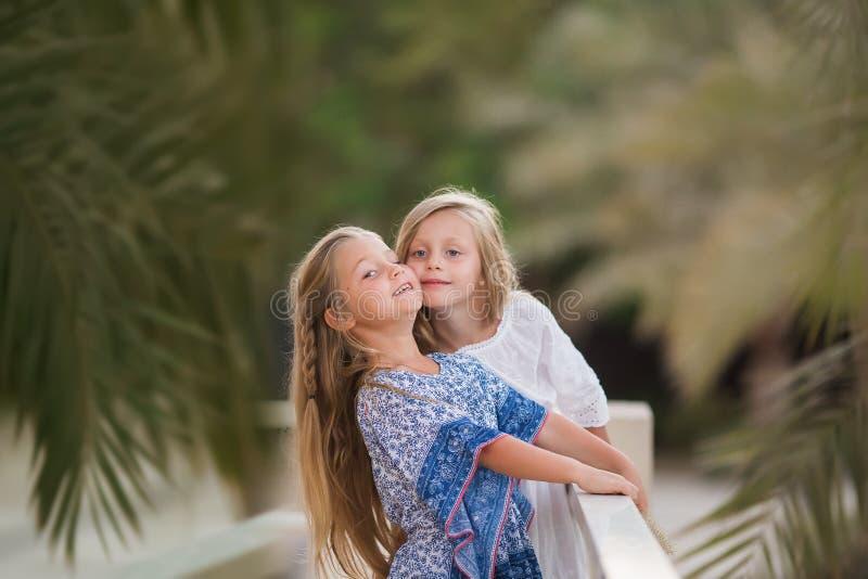 Dos muchachas felices como amigos se abrazan de manera alegre Peque?as novias en parque Amistad de los ni?os junto que sonr?e imagen de archivo