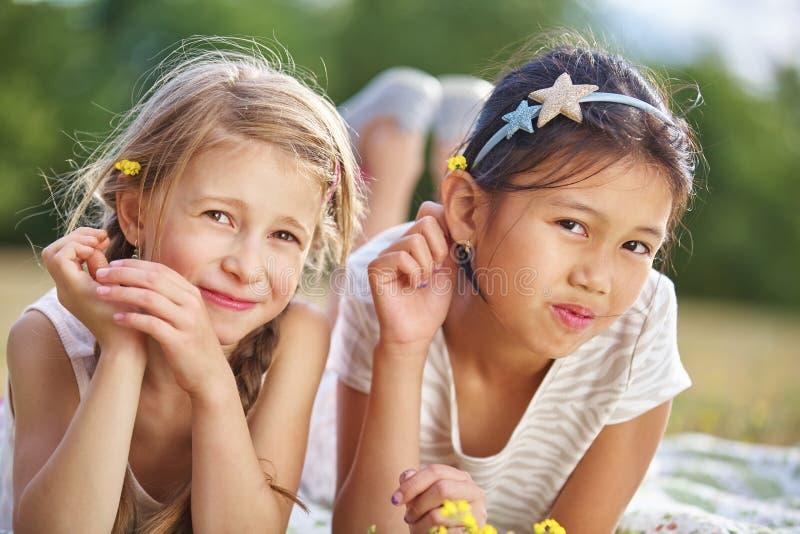Dos muchachas felices con las flores en su pelo fotografía de archivo libre de regalías