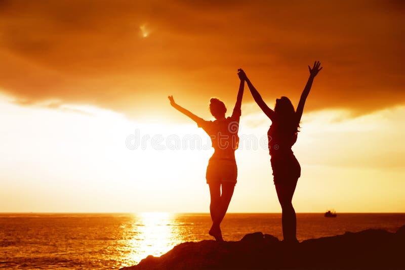 Dos muchachas felices con los brazos aumentados en el fondo del mar de la puesta del sol imagenes de archivo