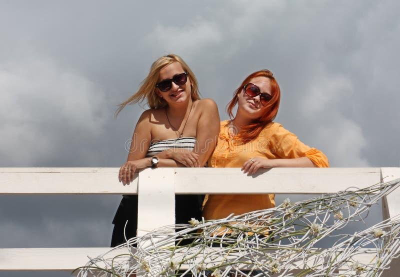 Dos muchachas felices en gafas de sol se colocan en el puente blanco imagenes de archivo