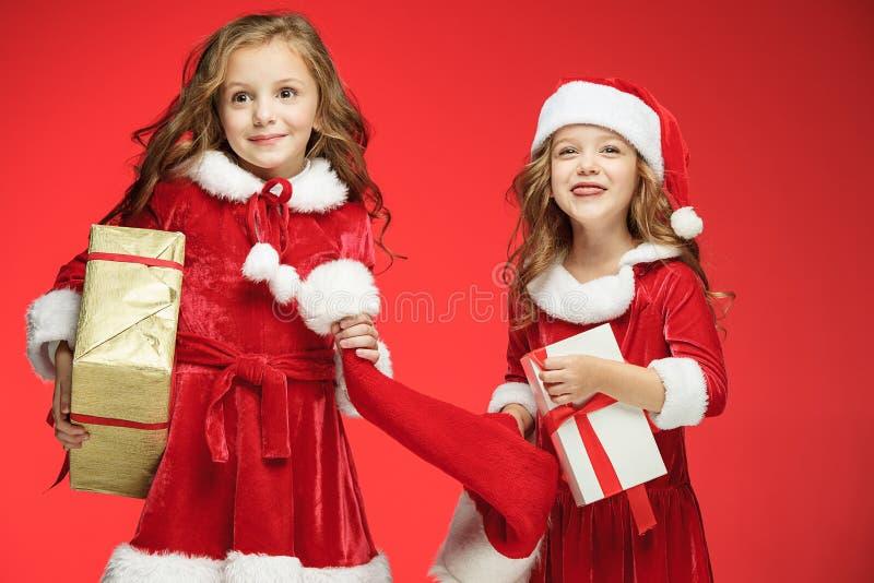 Dos muchachas felices en los sombreros de Papá Noel con las cajas de regalo en el estudio foto de archivo