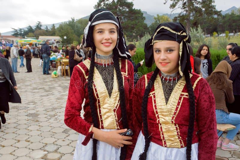 Dos muchachas felices en los trajes georgianos tradicionales listos para el funcionamiento durante partido en el día de la ciudad imagen de archivo