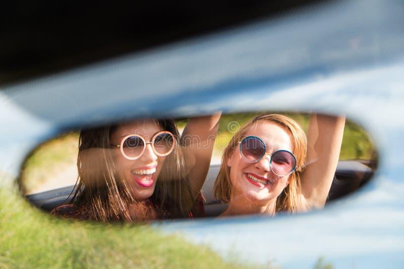Dos muchachas felices en un retrovisor del coche foto de archivo