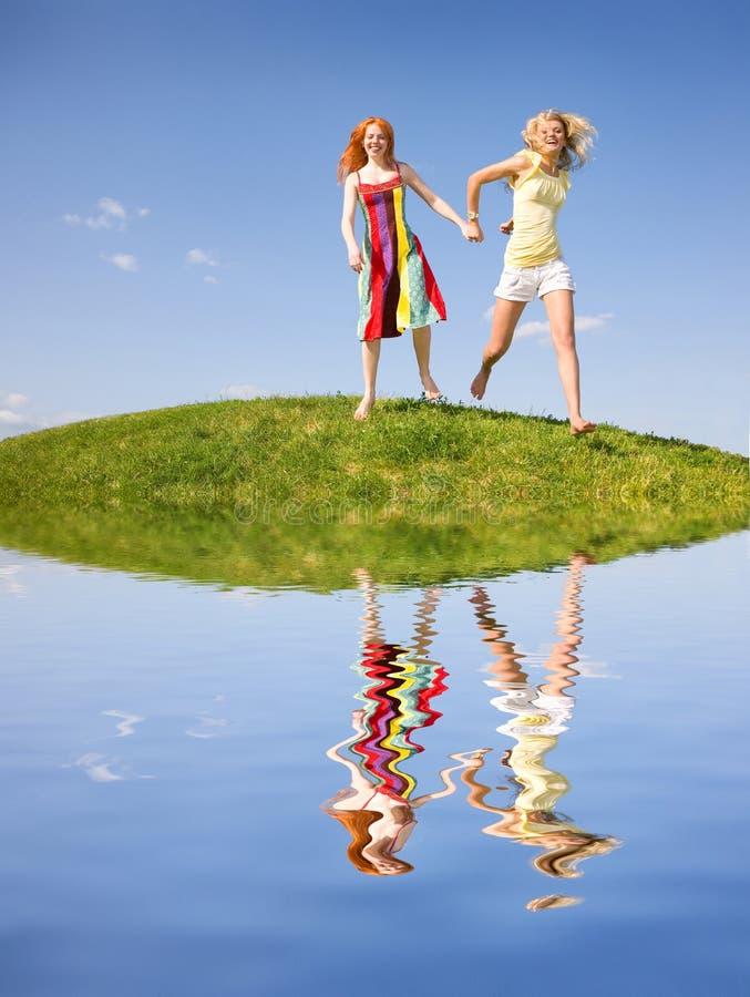 Dos muchachas felices que huyen en un prado foto de archivo