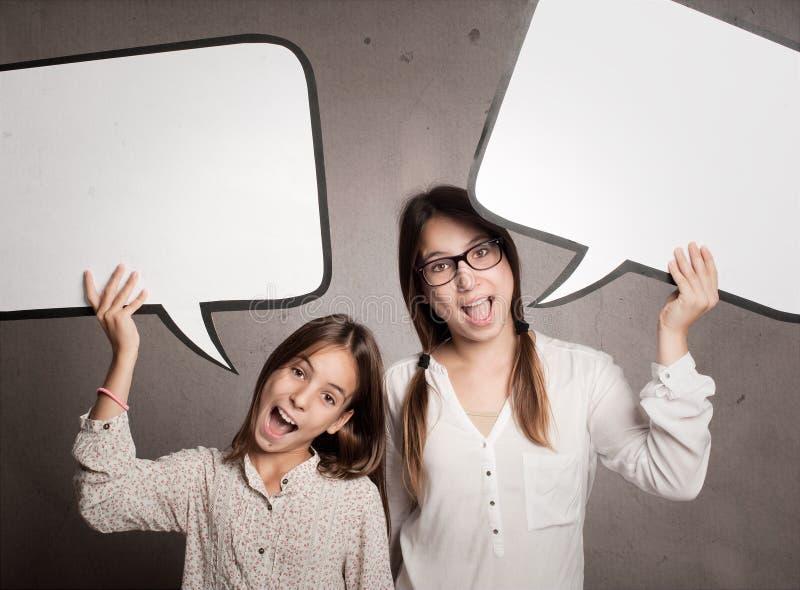 Dos muchachas felices que llevan a cabo una burbuja del discurso imagen de archivo libre de regalías