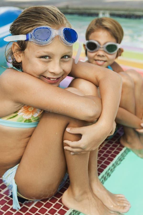 Dos muchachas felices que llevan gafas de la nadada por la piscina imágenes de archivo libres de regalías