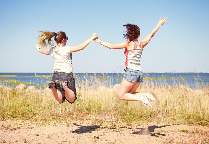 Dos muchachas felices que saltan en la playa fotografía de archivo