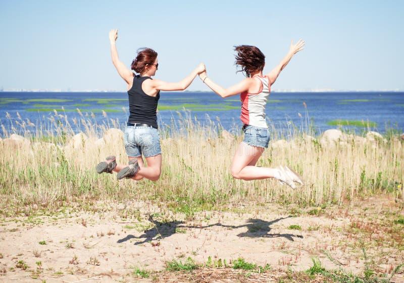 Dos muchachas felices que saltan en la playa imágenes de archivo libres de regalías
