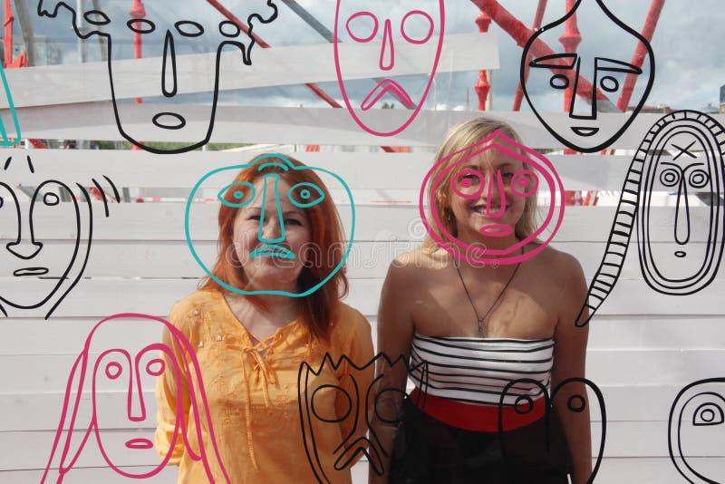 Dos muchachas felices sonríen detrás de la pared de cristal con las caras foto de archivo libre de regalías