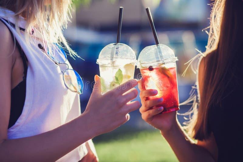 Dos muchachas frescas de moda del inconformista que llevan a cabo la bebida imagen de archivo